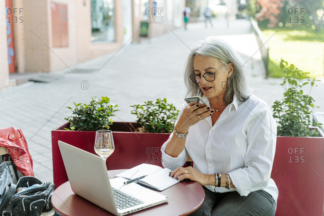 Busy middle aged female entrepreneur recording voice message on smartphone while working on project on terrace of cafe