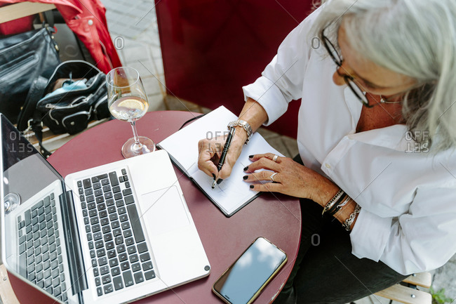 From above of crop middle aged female entrepreneur sitting at table in cafe and writing plans in organizer while working remotely