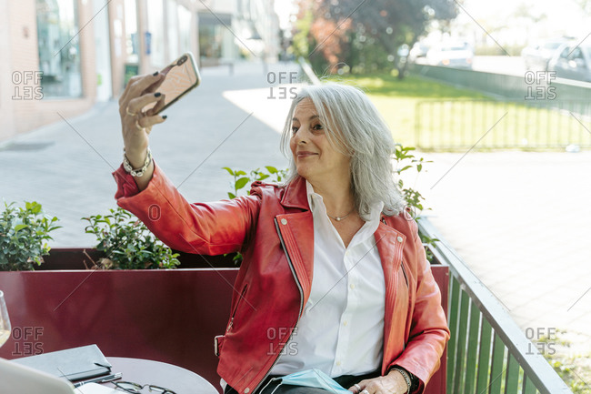 Delighted middle aged female with gray hair taking selfie on smartphone while sitting in outdoors cafe and waiting for order