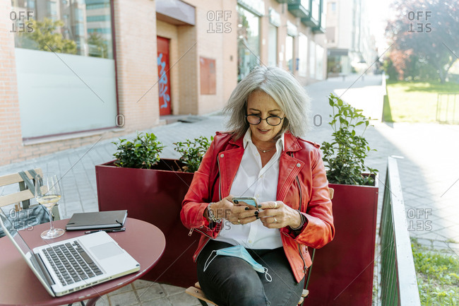 Busy middle aged female entrepreneur messaging on smartphone while working on project on terrace of cafe