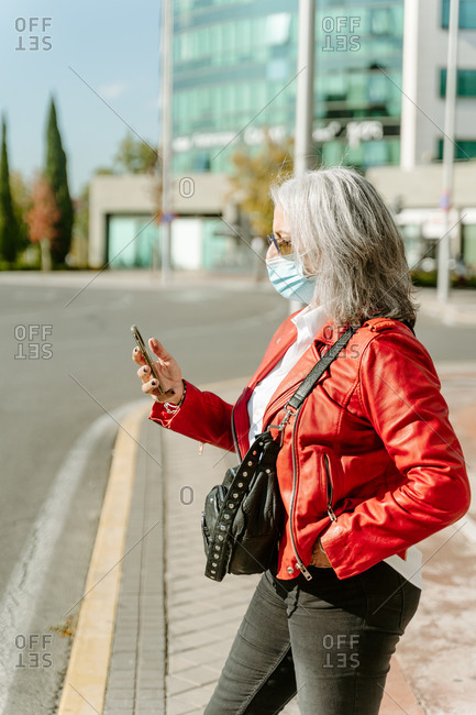 Side view of middle aged female in protective mask standing on street and browsing smartphone during coronavirus epidemic