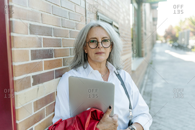 Confident middle aged female entrepreneur in smart casual style standing with laptop along street and looking at camera