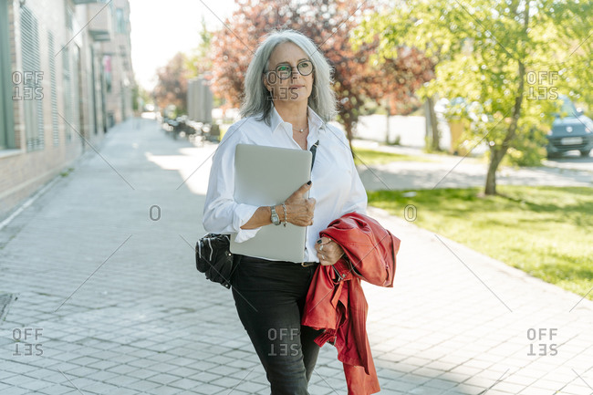 Confident middle aged female entrepreneur in smart casual style walking with laptop along street and looking away