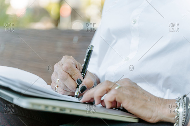 Cropped unrecognizable female entrepreneur in smart casual wear sitting on bench and writing list of daily routine tasks while working remotely in park
