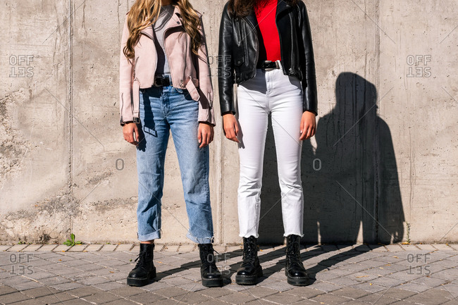 Unrecognizable crop female millennials in trendy boots and jackets standing on urban street on sunny day