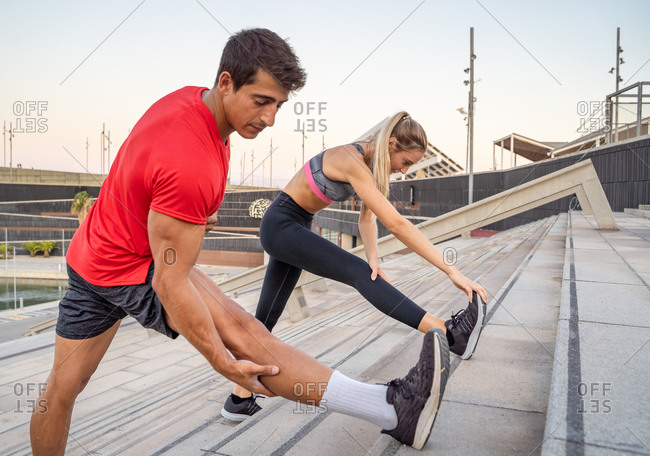 Side view of young determined sportswoman and sportsman standing on stairs and doing forward bends while stretching legs before workout