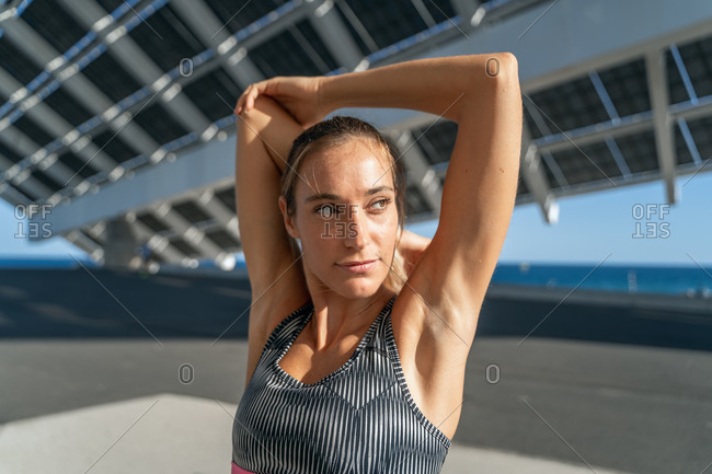 Charming female runner stretching arms while warming up before training and looking away