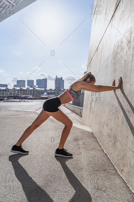 Side view of fit female athlete leaning on wall and stretching legs before active training on sunny day in city