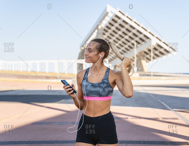 Smiling athletic female in summer sportswear enjoying songs in earphones during workout in city