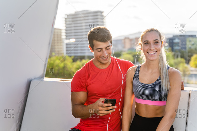 Young slim woman sportswear and strong muscular man listening to music on earphones on smartphone after fitness workout together in city