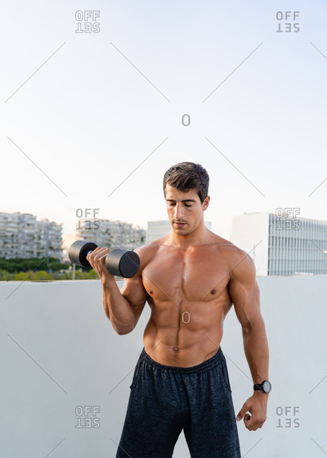Athletic muscular shirtless guy doing fitness exercise with dumbbell during intense workout in city