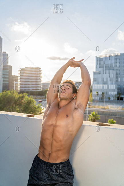 Muscular shirtless male standing near stone fence and stretching arms during warm up exercise before fitness training in city in summer day