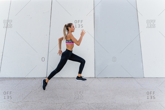 Side view of young fit female athlete in sportswear jogging during workout on city street and looking forward