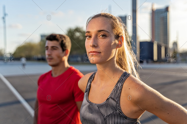 Young trendy female athlete looking at camera near fit boyfriend in town in back lit