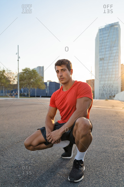 Muscular male athlete in sportswear and sneakers resting on asphalt road after workout in town while looking at camera
