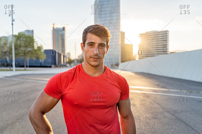 Crop masculine athlete with muscles looking at camera on asphalt roadway after exercising in town