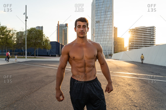 Crop masculine athlete with naked torso and muscles looking at camera on asphalt roadway after exercising in town