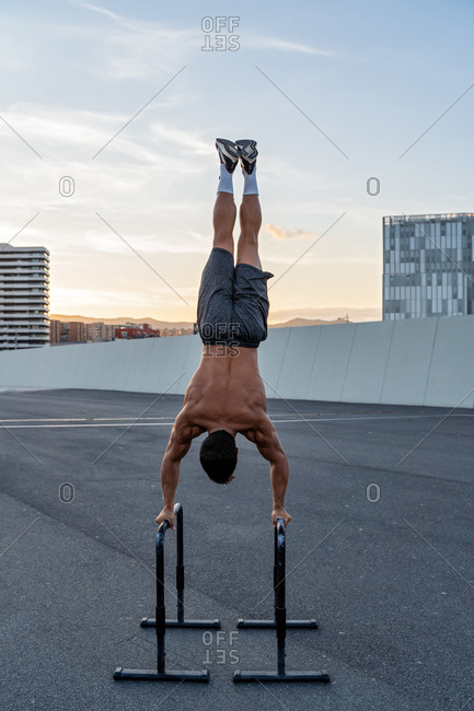 Unrecognizable muscular male athlete with naked torso performing handstand on bars on pavement in evening