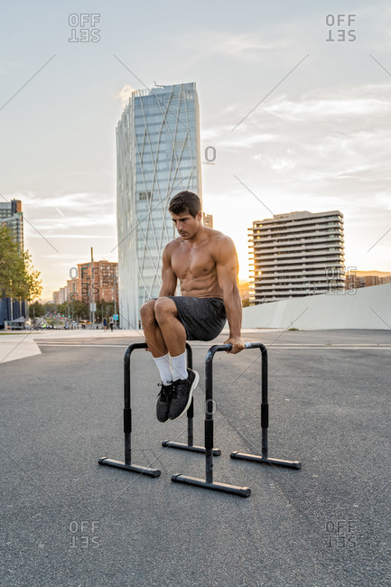 Fit male athlete with naked torso and muscles exercising on bars on road under cloudy sky in twilight