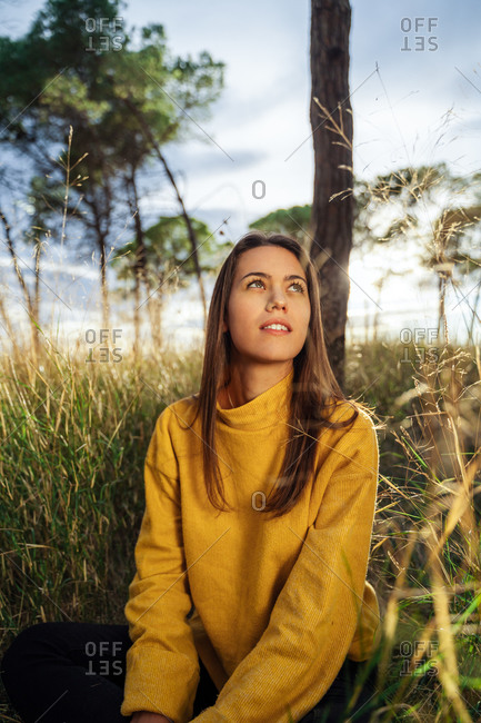 Tranquil female sitting in dry field and enjoying sunset in countryside while resting looking away