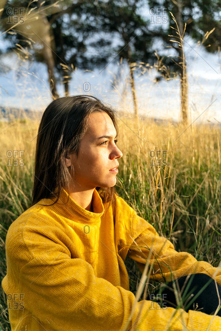 Side view of tranquil female sitting in dry field and enjoying sunset in countryside while resting looking away