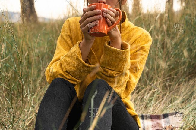 Cropped unrecognizable tranquil female sitting in field in autumn and drinking hot beverage while enjoying weekend