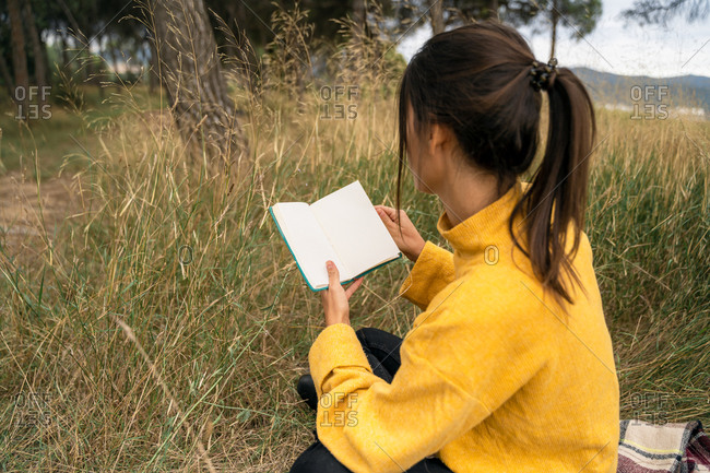 Side view of unrecognizable female sitting in filed in autumn and enjoying interesting story in book