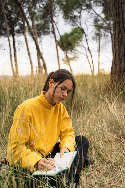 Peaceful thoughtful female sitting with crossed legs in dry meadow and writing thoughts in diary while relaxing at weekend in countryside