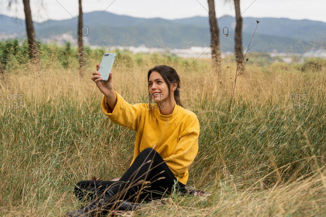 Side view of charming female in yellow sweater sitting in dry field and taking selfie while entertaining at weekend in countryside