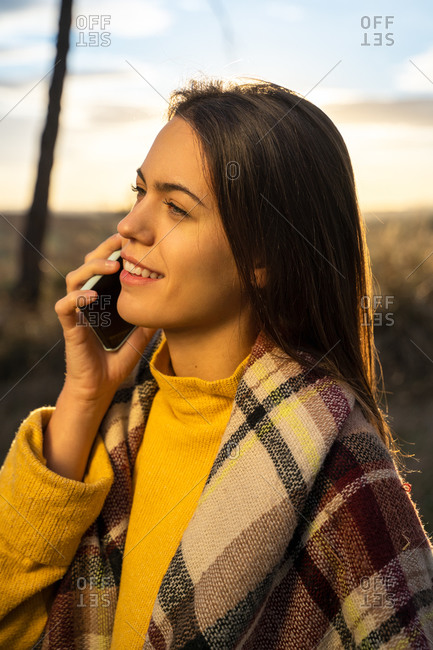 Side view of smiling female standing in autumn park and speaking on cellphone at sundown while looking away