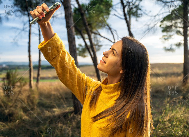 Side view of charming female in yellow sweater standing in dry meadow and taking selfie while entertaining at weekend in countryside