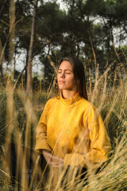 Tranquil female sitting in dry field and enjoying sunset in countryside with closed eyes while meditating