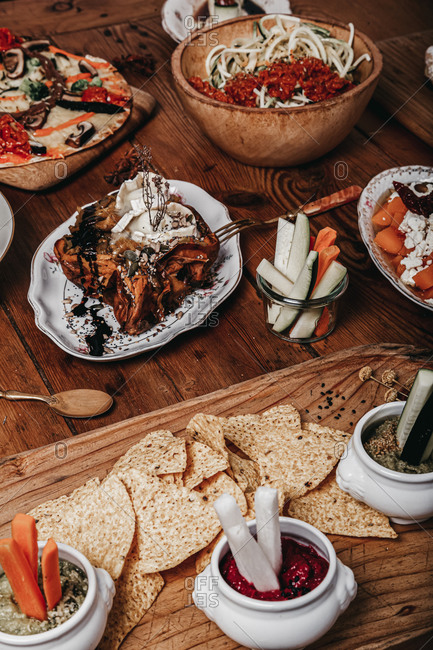 High angle of crunchy tortilla chips placed on wooden table with cucumber and carrot sticks in bowls with sauce