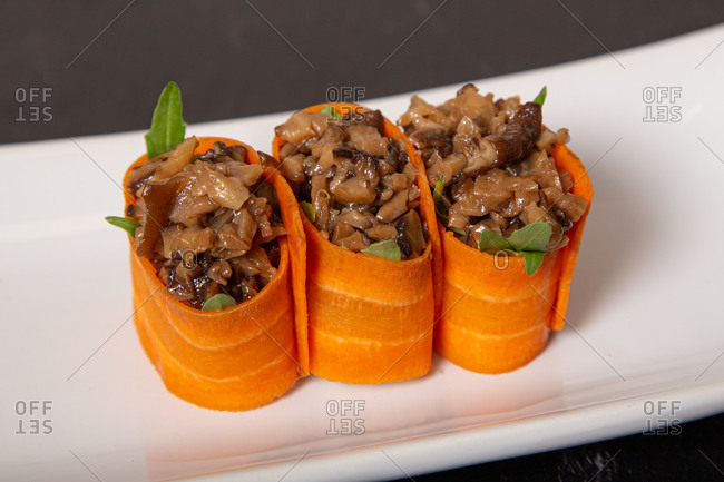 Closeup of delicious rolls made of carrots and chopped mushrooms served on plate in cafe