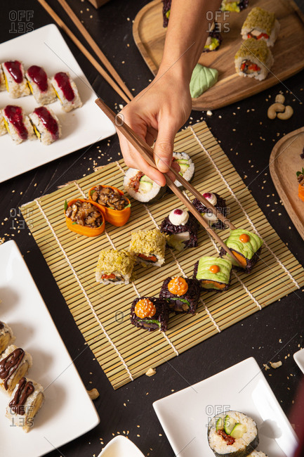 From above of crop unrecognizable hand with chopsticks taking assorted veggie sushi from bamboo mat