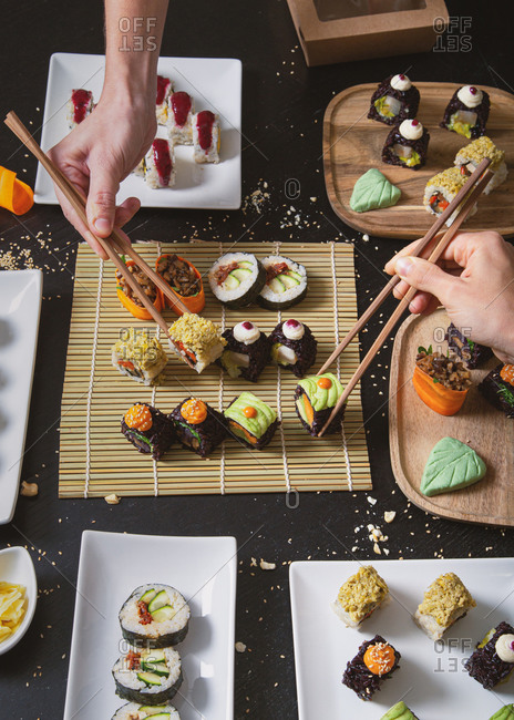 From above of crop unrecognizable people with chopsticks taking assorted veggie sushi from bamboo mat