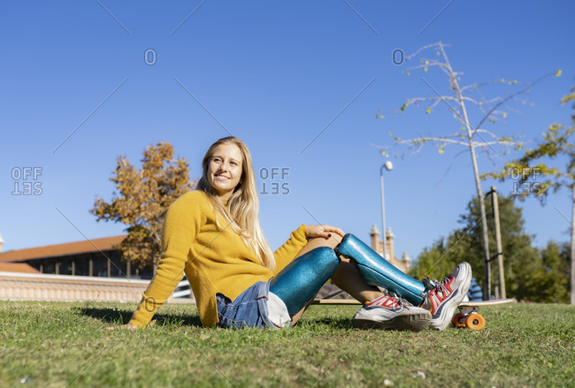 Joyful woman with leg artificial limb sitting on grass in park with longboard and relaxing on sunny day