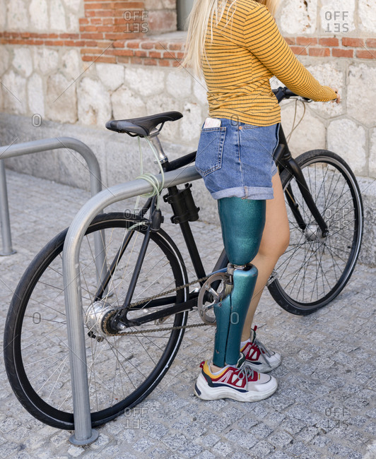 Side view of crop female with bionic leg prosthesis standing with modern bicycle on parking in city