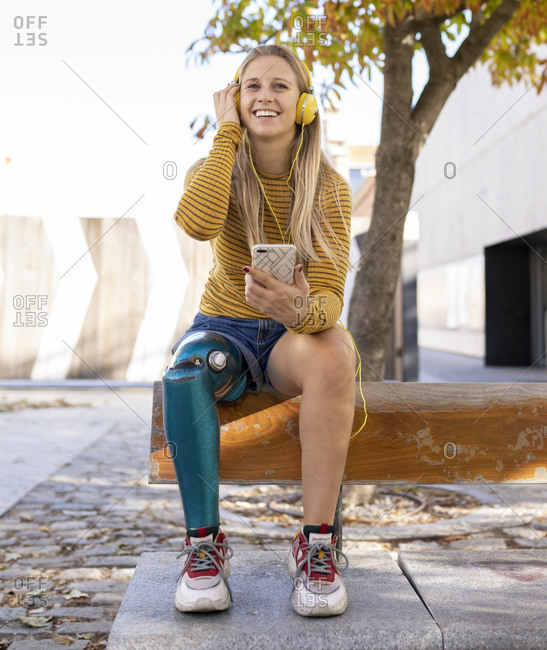 Front view of smiling female with bionic leg prosthesis sitting in street and enjoying music in headphones on sunny day