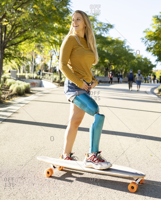 Side view of positive female with leg artificial limb of leg riding longboard on road in summer