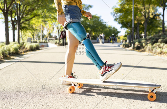 Crop side view of positive female with leg artificial limb of leg riding longboard on road in summer