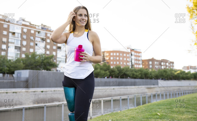 Front view of sportswoman with bionic artificial limb of leg standing on lawn in city and drinking fresh water during workout