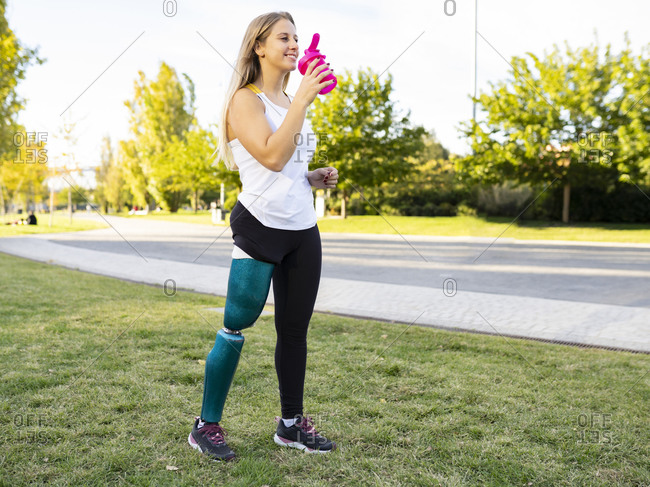 Side view of sportswoman with bionic artificial limb of leg standing on lawn in city and drinking fresh water during workout
