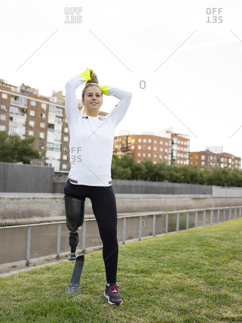 Delighted professional female runner with leg prosthesis making ponytail and preparing for training in city