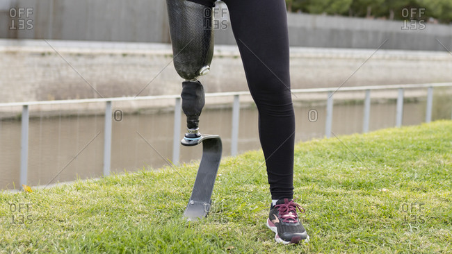 Front view of crop anonymous female runner with leg prosthesis exercising in park during active workout
