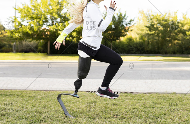 Side view of Paralympic female runner with artificial leg doing exercises on lawn in urban park during active training