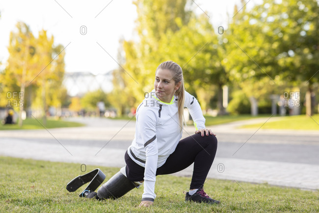 Focused Paralympic female runner with leg prosthesis stretching body and doing forward bend during training