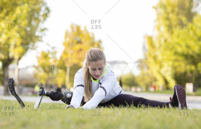 Smiling professional female sportswoman with artificial limb sitting on grass in park and stretching legs while doing forward bend during workout