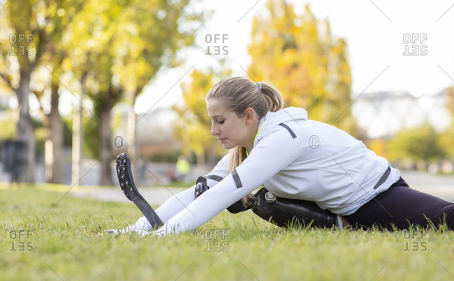 Professional female sportswoman with artificial limb sitting on grass in park and stretching legs while doing forward bend during workout