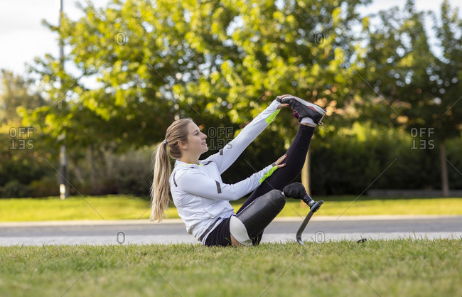 Side view of professional female runner with bionic prosthesis stretching legs during workout while sitting on grass